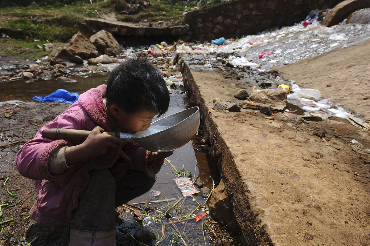 Un garçon boit de l'eau souillée